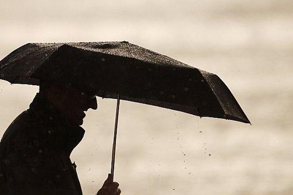 Un passant se protège de la pluie à Caen