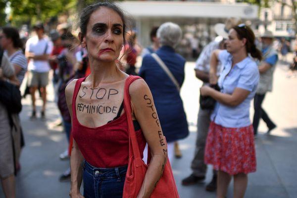 """Lors d'une manifestation, à Paris, une femme arbore le slogan """"Stop féminicides"""" sur la gorge."""