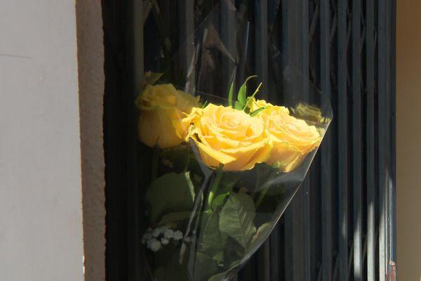 Des roses jaunes ont été accrochées sur les grilles de la laverie en hommage à la victime.