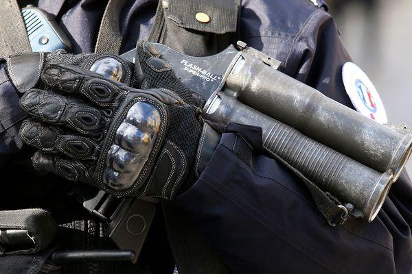 Policier tenant un lanceur de balles de défense / image d'illustration