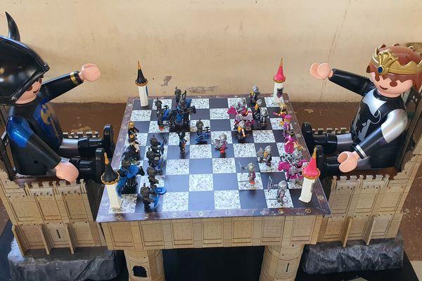 Un jeu d'échecs géant (les Playmobil assis sont à taille humaine). Les trônes et la table sont fabriqués avec des murs de château Playmobil.