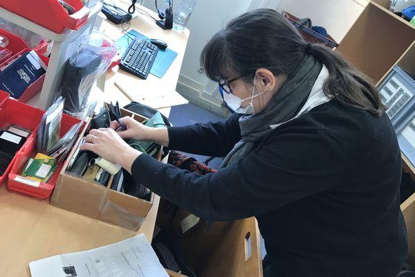 Nathalie, agent au service des objets trouvés cherche un porte-monnaie qu'on est venu réclamer.