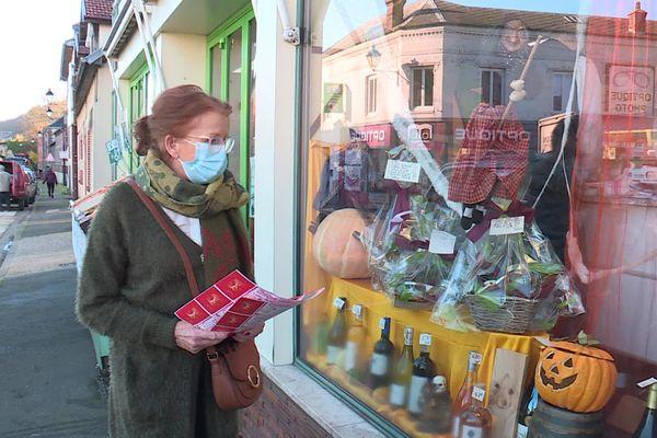"""18 Novembre 2020 : une cliente, un chèque cadeau en main, s'apprête à entrer dans un magasin de Charleval (Eure) qui participe à l'opération """"Solidarité commerces de proximité"""""""