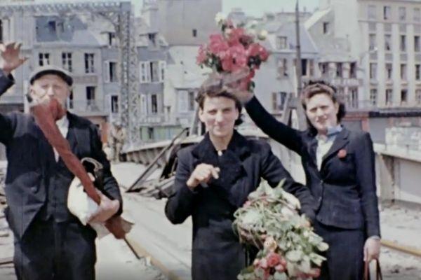 Sur le pont tournant dévasté à Cherbourg en 1944 , des civils saluant la fin de la guerre.