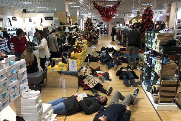 Allongés au sol, les militants sont restés silencieux pendant que les clients du magasin poursuivaient leurs achats.