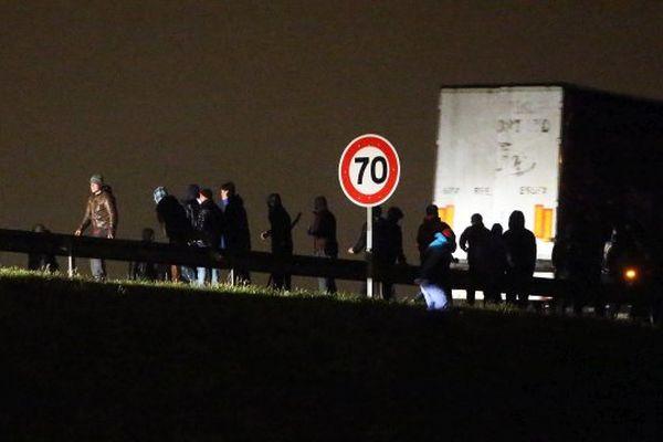 La nuit, les migrants tentent d'arrêter les poids lourds sur la rocade portuaire.