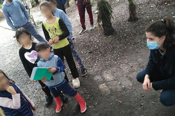Iris, à droite, distribue des activités aux deux élèves de l'école maternelle où elle enseigne. Il vivent dans un squat toulousain.