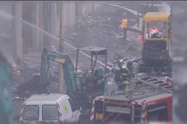 Un pompier éteint l'incendie dans un paysage dévasté par le souffle de l'explosion.