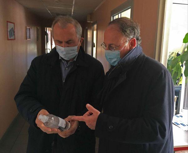 Le professeur Pierre Fréger  du CHU de Rouen et Laurent Dérolez directeur de Novacel à Déville examinent un flacon de gel hydroalcoolique produit dans l'usine de Déville-lès-Rouen (Seine-Maritime)