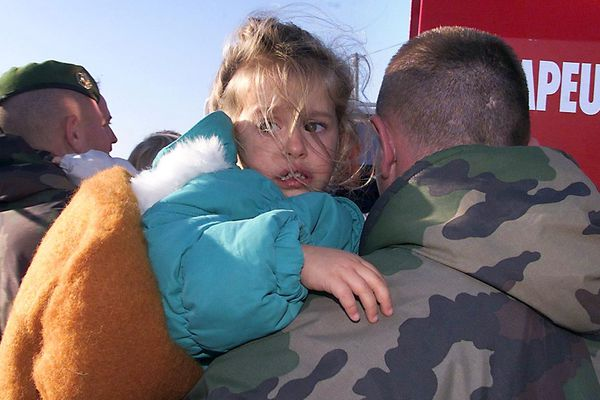 Un militaire porte une enfant qui vient d'être évacuée d'une habitation inondée, le 14 novembre 1999 à Cuxac-d'Aude, dans la zone du département la pus touchée par les inondations des derniers jours provoquant la mort de 26 personnes et des dégâts matériels importants.