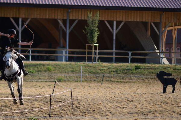 Un participant vise une cible depuis son cheval au galop.