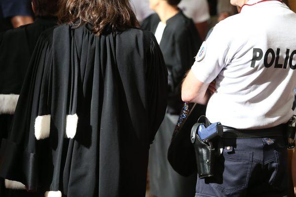 Une avocate en robe accompagnée d'un policier, de dos - Photo d'illustration