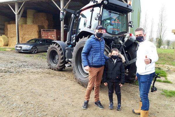 Le YouTubeur Thierry Bailliet pose devant son tracteur, avec l'administrateur de Agriculteur de Bretagne et son fils Enzo dans un élevage laitier à Saint-Symphorien (Ille-et-Vilaine) mercredi 3 mars 2021.