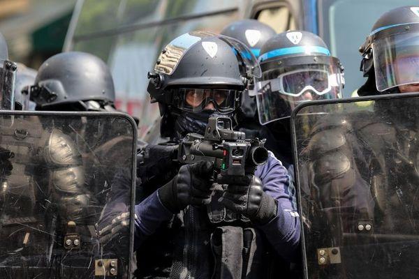Un policier pointe un LBD 40 lors d'une manifestation du 1er mai à Paris.