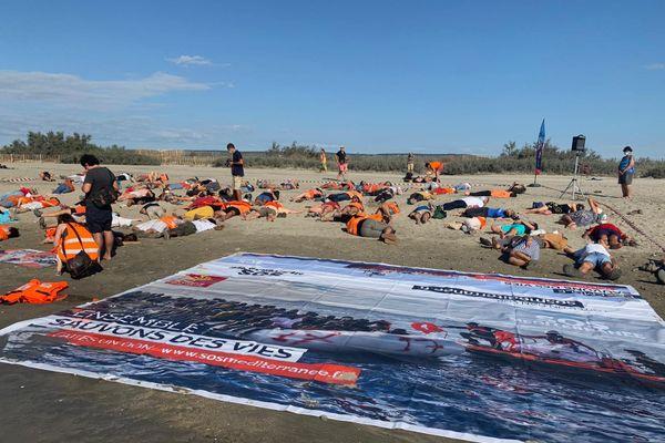 """Des dizaines de personnes de l'ONG SOS Méditerranée se sont allongées sur le sable ce matin aux Aresquiers pour l'opération """"die-in""""- 27 août 2020"""