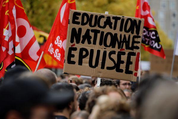 """Un manifestant brandissant une pancarte """"Education nationale épuisée"""" lors d'une manifestation des professeurs et directeurs d'école le 3 octobre 2019 à Bibigny (Île-de-France)."""