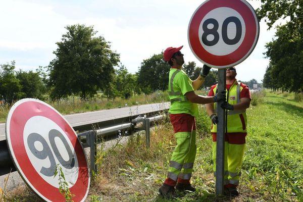 Deux ouvriers changeant un panneau dans le Haut-Rhin en juin 2018.