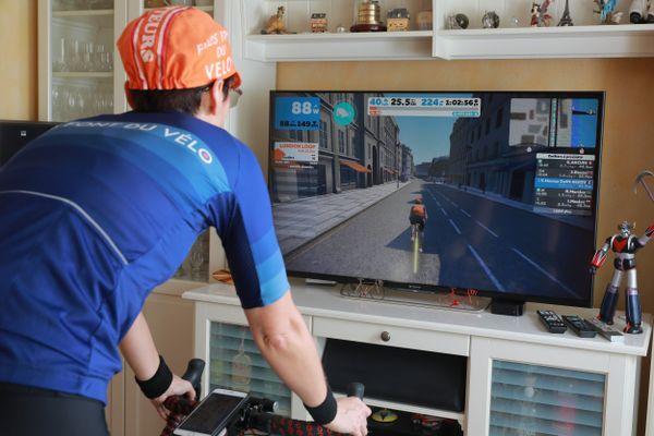 Muriel cycliste amateur sur son home trainer à son domicile utilisant l'application ZWIFT en ligne - sur son téléviseur - qui réunit les cyclistes du dimanche.