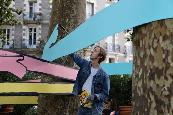 """Jean Jullien en train de peindre son oeuvre """"Les Enrouleurs"""""""