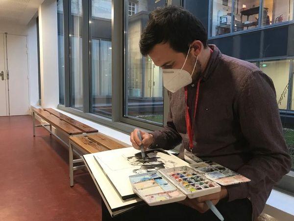 Valentin Pasquier peaufine un dessin dans les couloirs du tribunal.