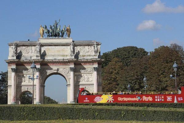 Un bus de la compagnie City Sightseeing Paris devant l'Arc de triomphe du Carrousel du Louvre, en 2016.