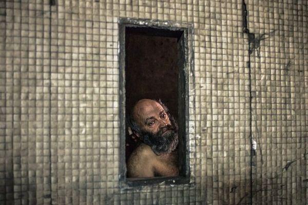 04/12/2012 - France / Ile-de-France / Paris - Henri regarde à travers une ouverture du tunnel qui passe sous l'avenue des Champs Élysées où il vit depuis plus quatre ans. Le regard perdu.