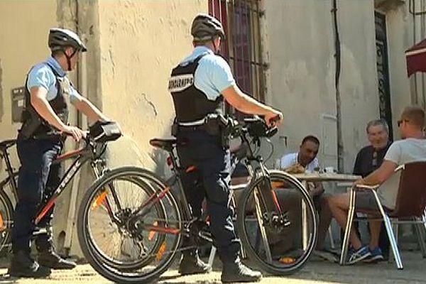 Deux gendarmes patrouillent à VTT dans le centre-ville de Vauvert. Gard. Août 2015.