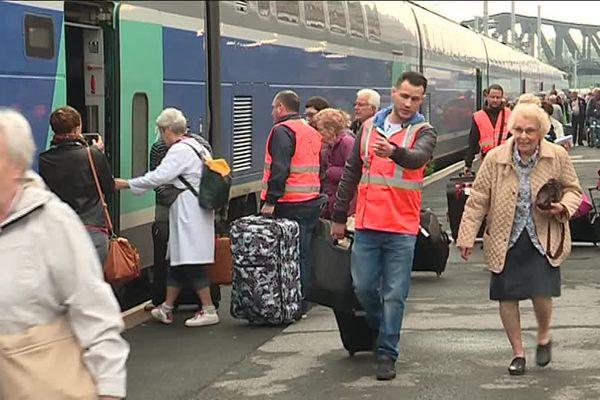 Valenciennes :  des cheminots grévistes aident des pélerins à prendre leur train pour Lourdes.