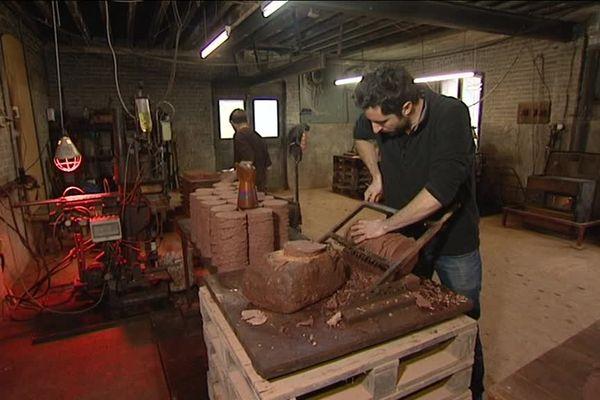 Découper l'argile du pays de Bray, première étape de la fabrication des fameuses tomettes.
