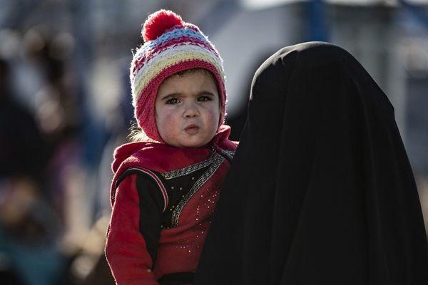 Une femme porte son enfant en attendant son départ lors de la libération d'un autre groupe de familles syriennes du camp d'al-Hol géré par les Kurdes, qui détient un parent présumé de combattants du groupe État islamique (EI), dans le gouvernorat de Hasakeh, dans le nord-est de la Syrie, le 20 février 2021.