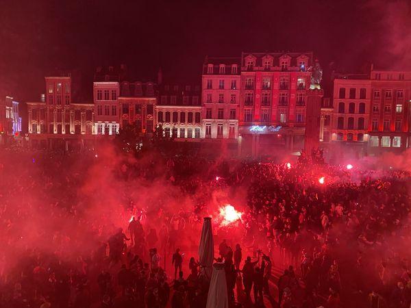 Des milliers de supporters fêtent le titre de champion du LOSC sur la Grand Place dans un nuage de fumée rouge.