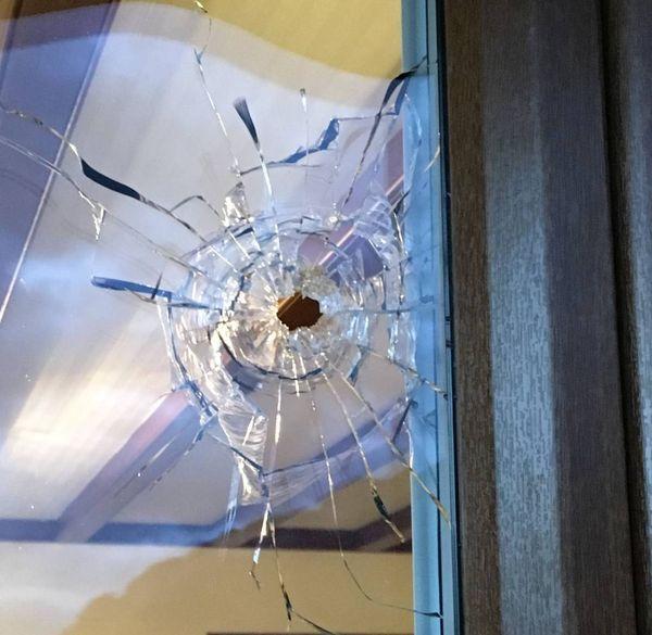 La balle a traversé la baie vitrée du salon puis elle a ricoché contre un mur.