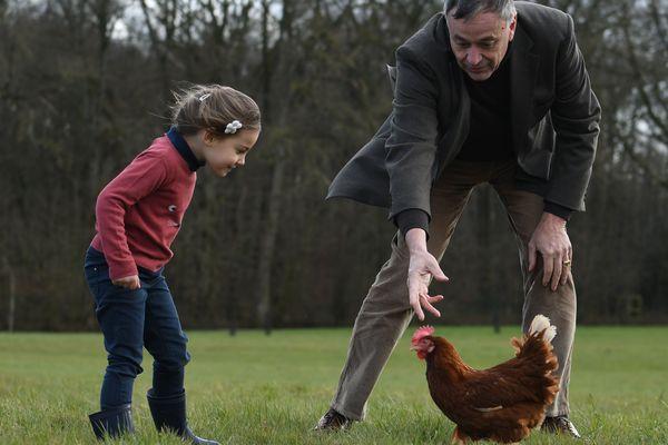 Yves de la Fouchardière avec Agathe, la poule rousse offerte à Emmanuel Macron et Agathe, la petite fille illustrant les boites d'oeufs de Loué