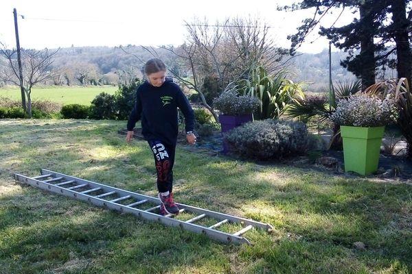 Avec les moyens du bord, ici Angelina joueuse de handball à Fouesnant s'entraîne avec une échelle, pour rester en forme pendant le confinement