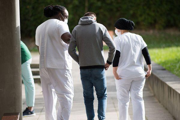- Photo d'illustration - Un patient se promène avec des membres du personnel médical