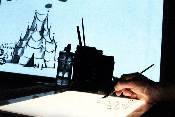 Avec des petits bonhommes en carton et des décors en papier qu'ils manipulent sur une table rétro éclairée, la compagnie Stereoptik construit en direct et sous les yeux du public, un film d'animation à l'ancienne.