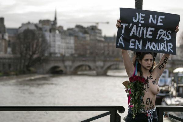 Une militante des Femen enchaînée à un lampadaire, avec une pancarte indiquant : « Je ne t'aime pas à en mourir ».