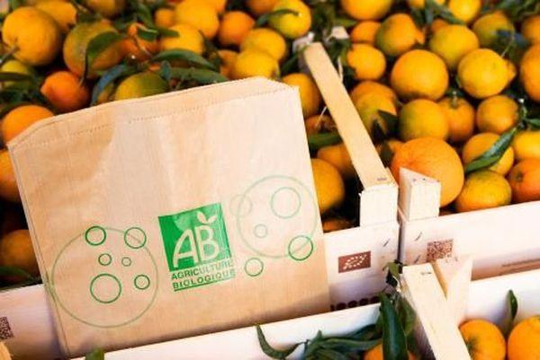 """Des cagettes de clémentines bio et des sacs en papier avec le logo """"Agriculture Biologique""""."""