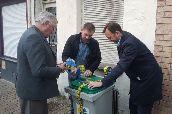 Le maire François Decoster (à droite) scotche une poubelle laissée devant une maison de Saint-Omer