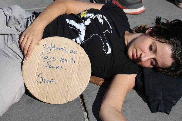 """Une femme avec une pancarte : """"Un féminicide tous les 3 jours. Stop"""""""