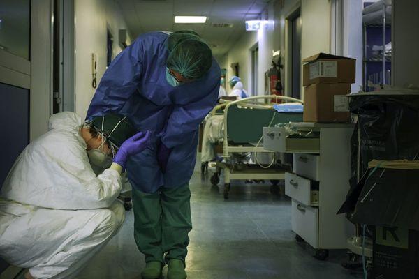 """En Italie, le Covid-19 a fait des milliers de morts. L'épidémie n'a de cesse d'évoluer et oblige désormais les soignants à faire """"le tri"""" dans les patients. Sur cette photo de Paolo Miranda, des soignants épuisés. La France se prépare à un pic similaire. Les soignants, déjà épuisés, alertent le gouvernement. Ils appellent aussi les Français à respecter très strictement le confinement pour ne pas les mettre en difficulté."""