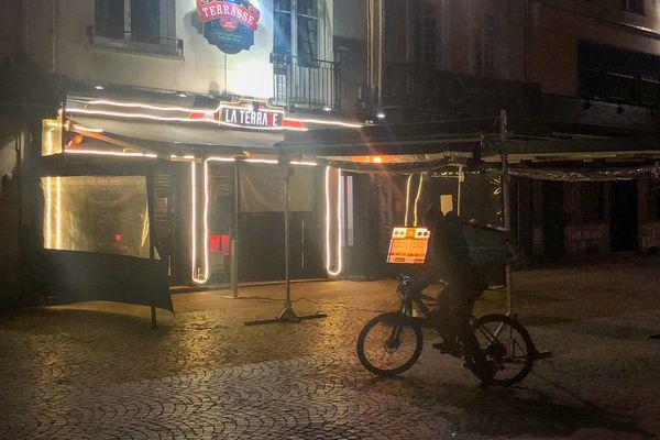 Devant la Terrasse à Rouen, un livreur Deliveroo vient chercher des commandes de burgers.