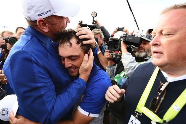 Le golfeur italien Francesco Molinari (au centre) célèbre la victoire de la Ryder Cup dans les bras du capitaine de l'équipe européenne, le Danois Thomas Bjorn, le 30 septembre 2018.
