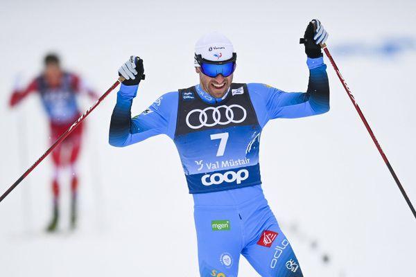 Maurice Manificat lève les bras après sa troisième place sur l'épreuve de la poursuite lors de l'étape de coupe du monde de Val Muestair en Suisse, le 3 janvier 2020.