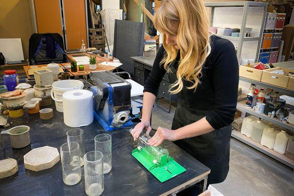 Jennifer Gaspard dans son atelier, les bouteilles récupérées sont retaillées à la main avant d'intégrer ses créations