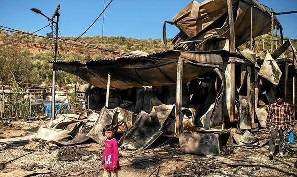 Au lendemain de l'incendie, quelques demandeurs d'asile errent dans le camp dévasté, à la recherche de ce qu'ils pourraient retrouver de leurs maigres affaires