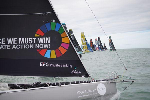 """En premier plan, l'Imoca Malizia II du yachtclub de Monaco rase de très près le bateau arbitre. Sur sa voile on peut lire  le slogan """" a race we must win"""""""