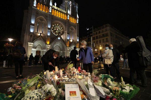 Des passants allument des bougies devant la basilique Notre-Dame, à Nice, le soir de l'attentat.
