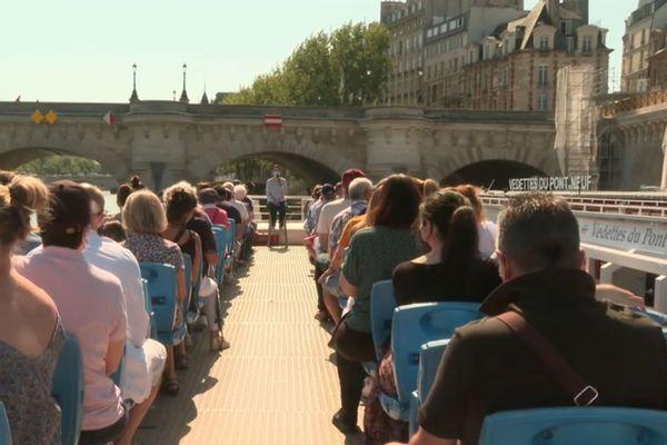 Des touristes à bord d'une vedette, sur la Seine.