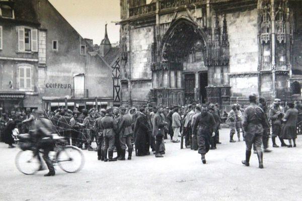 Des soldats métropolitains dans un enclos de barbelés place de la mairie à Clamecy (Nièvre). Photographie non datée